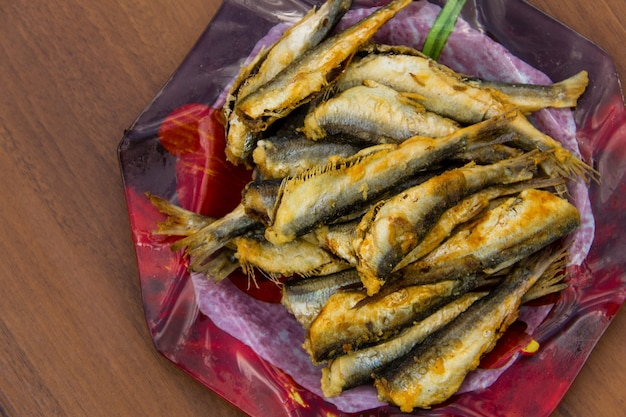 Fried baltic herring on a plate on wooden background