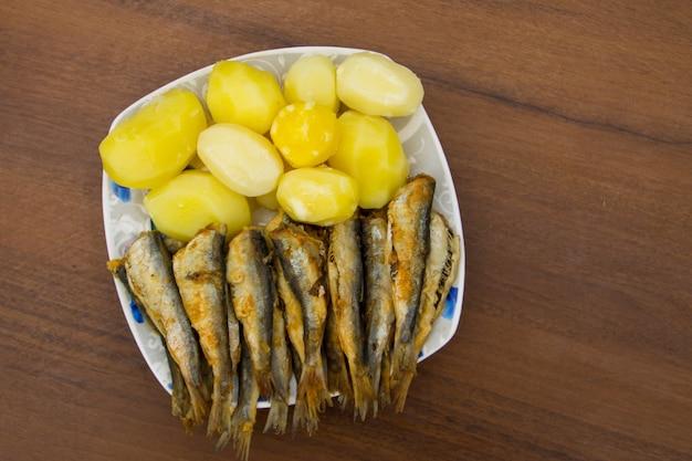 木製の背景のプレートに茹でたジャガイモと揚げバルト海ニシン