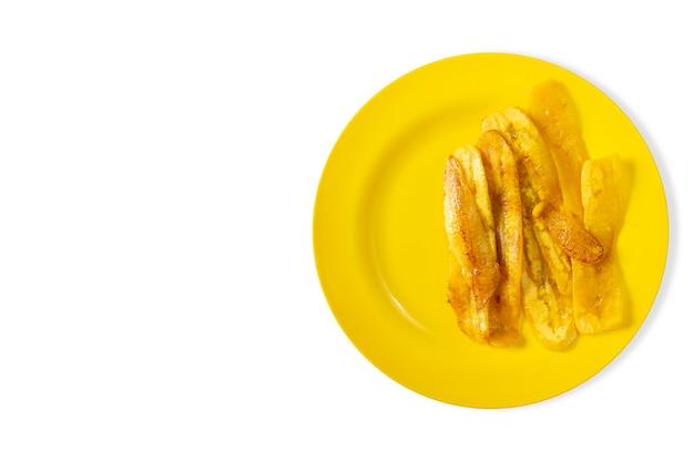 Жареный банан на желтой тарелке на желтом фоне