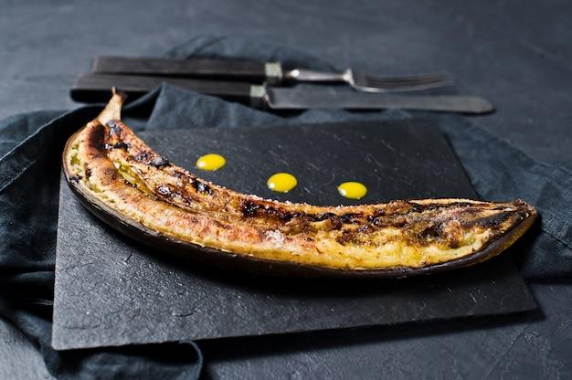 Fried banana with honey on a black stone board.