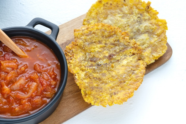 Fried banana with tomato sauce in a dark pot on a kitchen table with a white surface. latin cuisine concept.