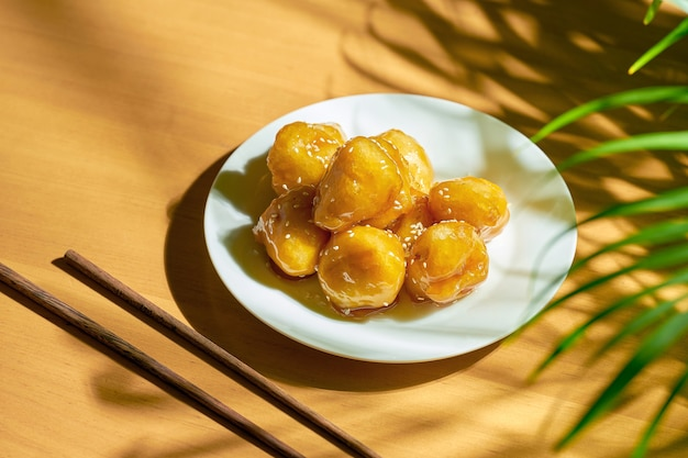 Жареные бананы в карамели и кляре с кунжутом в белой тарелке. китайский рецепт и кухня