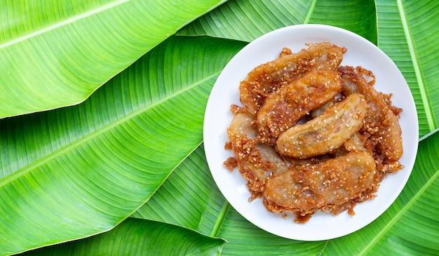 バナナの葉の表面の白いセラミック丸皿にゴマと揚げバナナ