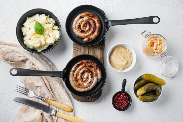 ザワークラウトとバイエルンのドイツのニュルンベルガーソーセージの揚げ物、鋳鉄製フライパンのマッシュポテト、白い背景、上面図フラットレイ