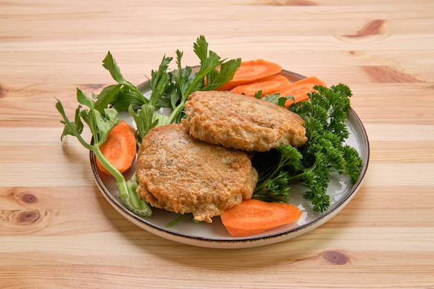 Fried beef cutlet in breading with fresh carrot