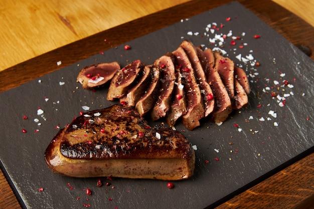 Жареная говяжья печень нарезанная на черной доске