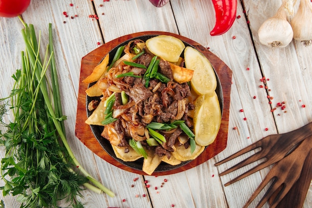 Fried beef meat with potato on the wooden table