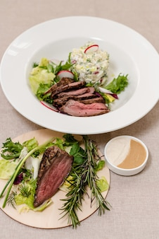 Жареная говядина на тарелке с ингредиентами для окрошки и зеленью ресторанная концепция приготовления