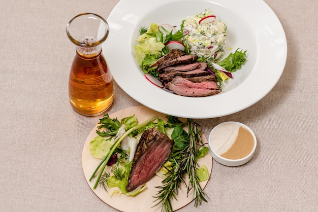 Жареная говядина на тарелке с ингредиентами для окрошки и графином кваса