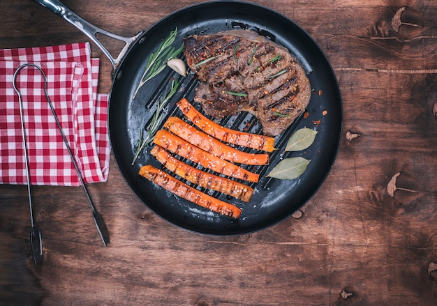 Fried beef stack and fried carrots on a round frying pan
