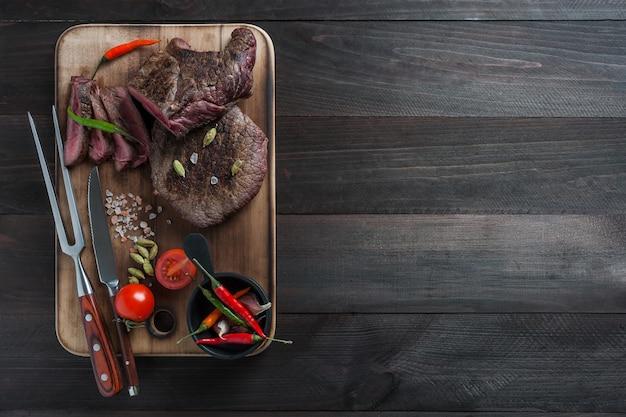 Жареный стейк из говядины на деревянной доске. горячие встречаются с овощами и специями. выборочный фокус