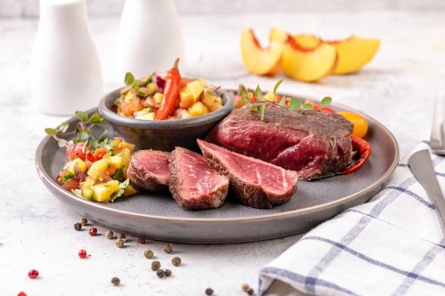 Жареный стейк из говядины с сальсой из плодов персика, помидорами и чили. средний или редкий жареный стейк нарезать кусочками. готовы есть. крупный план.