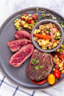 ピーチフルーツサルサ、トマト、チリを添えたビーフステーキのフライ。ミディアムまたはレアのフライドステーキを細かく切ったもの。食べる準備ができました。上面図。