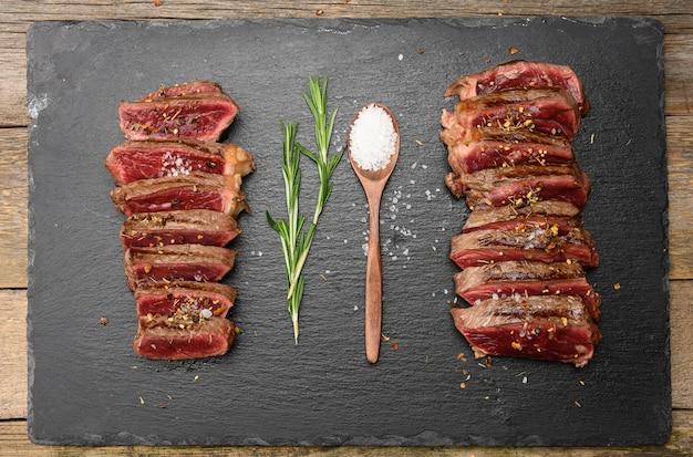Жареные говяжьи стейки, нарезанные кусочками на черной доске, степень прожарки, редкая с кровью, вид сверху
