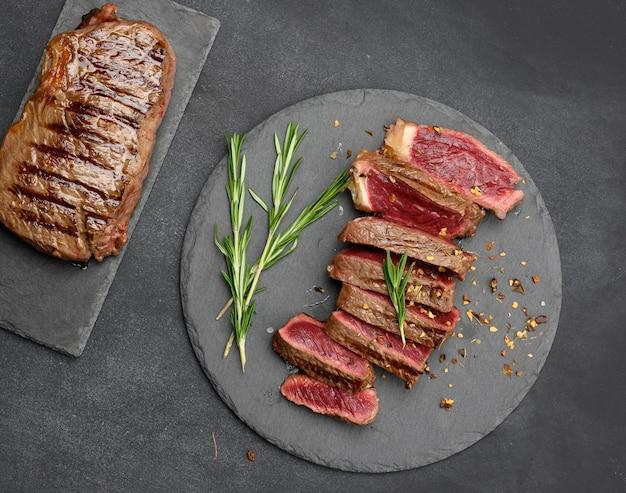 튀긴 쇠고기 스테이크는 블랙 보드에 조각으로 잘리고 피가 거의 없는 익힘 정도, 위쪽 전망