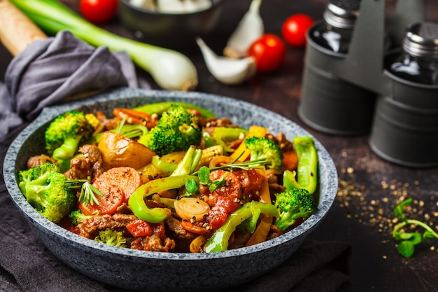 Fried beef stroganoff with potatoes, broccoli, corn, pepper, carrots and sauce in a pan