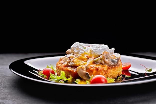 キノコ、ポーチドエッグ、トマトの黒皿に揚げたステーキ