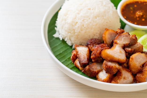 아시아 스타일의 매운 소스를 곁들인 밥과 튀긴 배꼽 돼지 고기