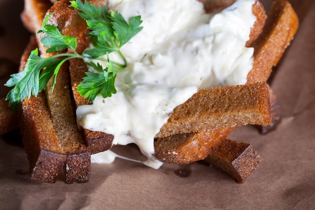 Fried black bread, croutons with creamy garlic sauce, food a quick snack in a cafe