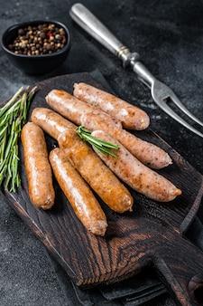 Жареные сосиски bratwurst или хот-доги на деревянной доске. вид сверху.