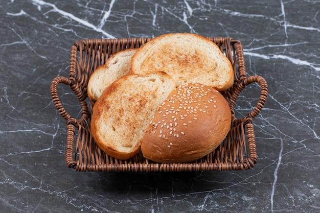 Жареный хлеб и булочка в плетеной корзине.