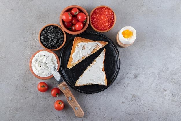 Жареный хлеб с вареными яйцами и красными свежими помидорами черри.