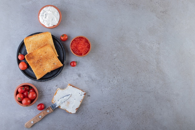 Fried bread with caviar and red cherry tomatoes placed on marble background.