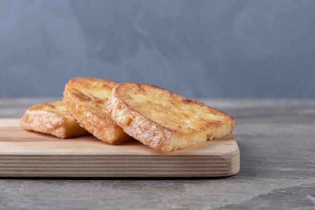 Жареный хлеб с яйцом на деревянной доске.