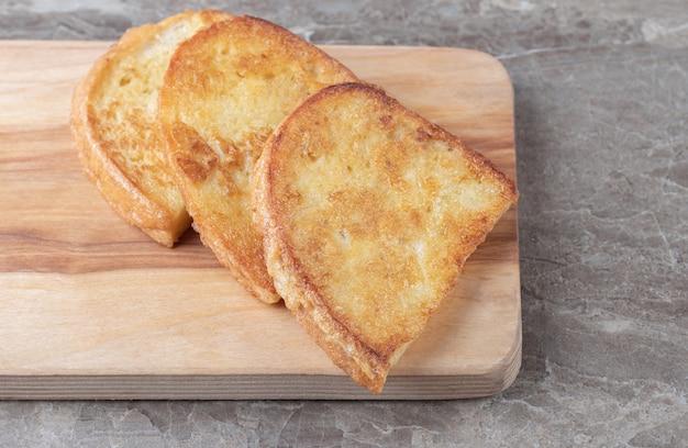 Pane fritto con uovo su tavola di legno.