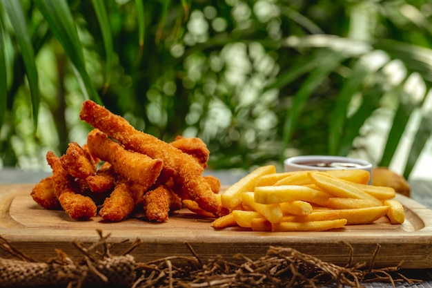 Fried breaded chicken breast strips with ketchup and french fries on a wooden board