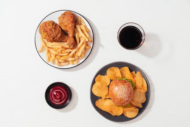 튀긴 빵가루 입힌 바삭한 치킨 너겟과 감자튀김을 나무 접시에, 케첩과 청량 음료를 옆에
