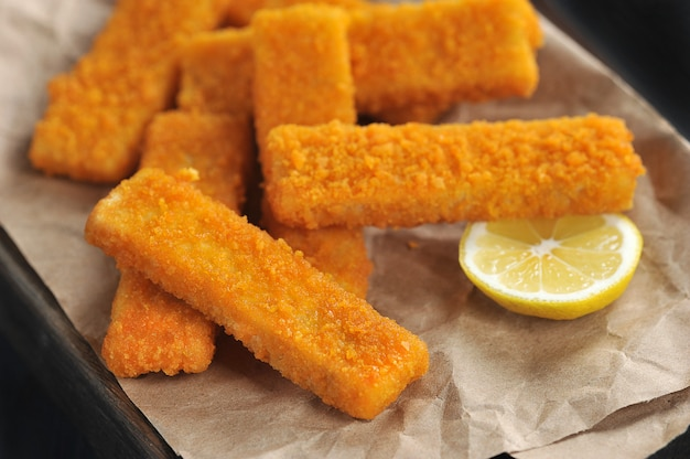 Fried breaded fish sticks and lemon on paper
