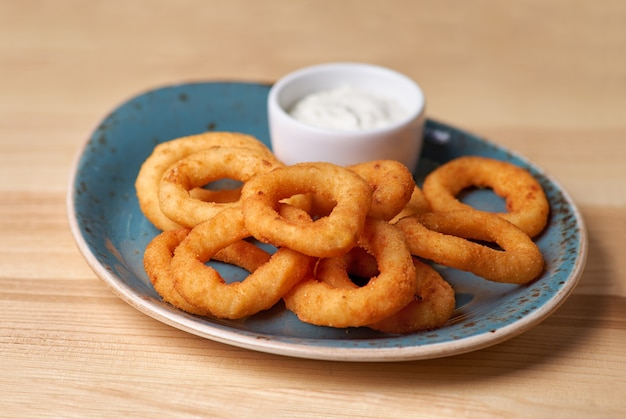 Fried breaded onion rings with sauce. on wooden table
