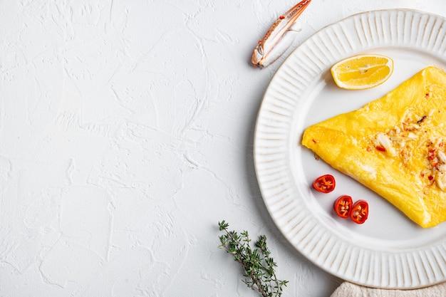 カニ肉とチーズの揚げ朝食オムレツ、プレート、白い背景、上面図フラットレイ、コピースペースとテキスト用のスペース