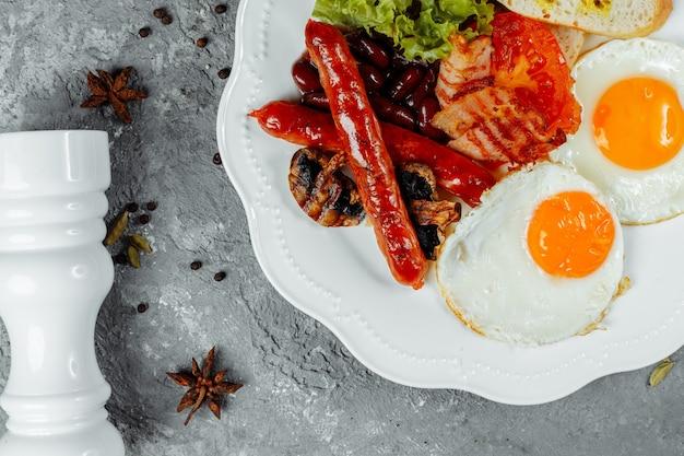 Жареный завтрак с беконом, сосисками и запеченной фасолью.