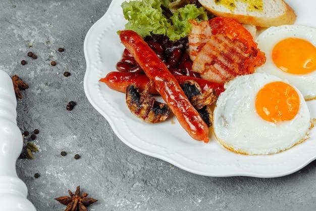 Жареный завтрак с сосисками из бекона и запеченной фасолью