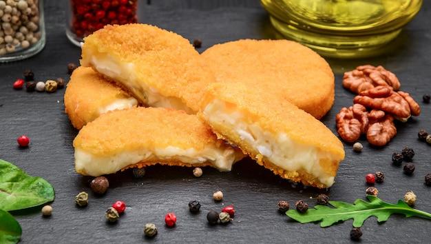 黒い石のボードにバッターで揚げたブリーチーズ。カマンベールチーズ