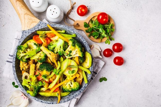 Fried broccoli, peppers, corn, zucchini and tomatoes in pan on a white background.