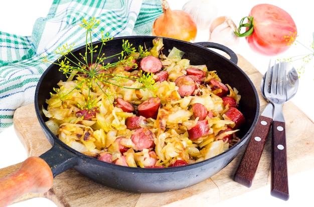 Fried cabbage with smoked sausages in pan
