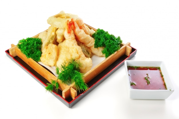 Fried calamari with parsley and dill in a decorative wooden plate. on a white wall.