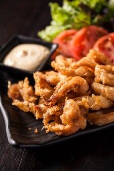 Жареный кальмар с соусом и салатом
