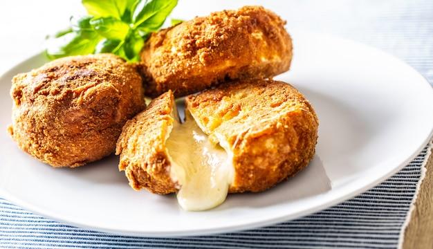 크랜베리 잼과 바질을 곁들인 튀긴 카망베르 또는 브리 치즈.