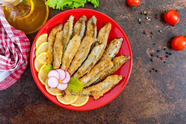 赤いプレートにレモンとカラフトシシャモの炒め物。小さな海の魚の料理。上面図。フラットレイ