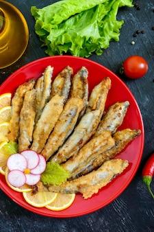 黒い木製の背景の上の赤いプレートにレモンと揚げカラフトシシャモ。小さな海の魚の料理。上面図。フラットレイ