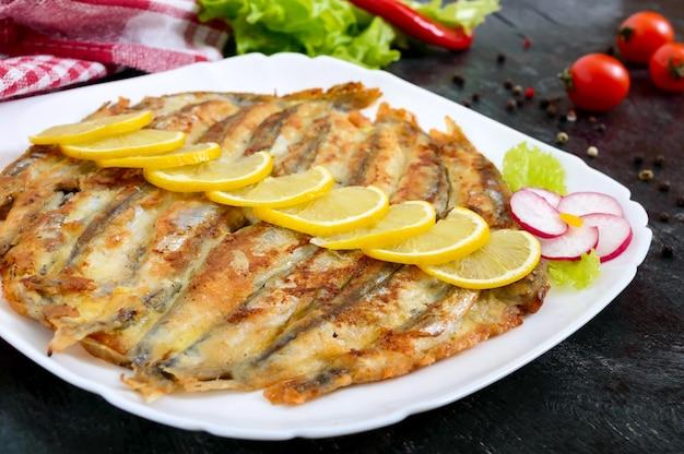黒い木製の背景に白いプレートにレモンと揚げカラフトシシャモ。小さな海の魚の料理。閉じる