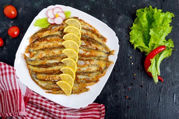 黒い木製の背景に白いプレートにレモンと揚げカラフトシシャモ。小さな海の魚の料理。上面図。