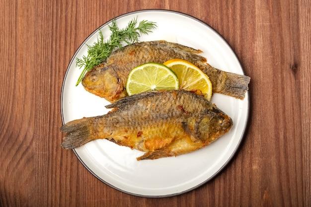 레몬과 라임 조각, 평면도와 하얀 접시에 튀긴 잉어 물고기. 준비된 식사. 나무 배경