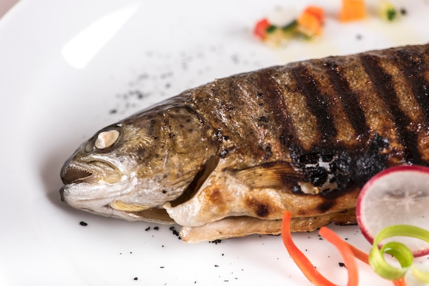 Fried carp with lemon,  decorated with herbs,  isolated on light background