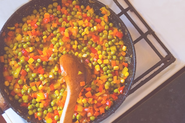 Fried carrots with peppers and peas on the old pan.