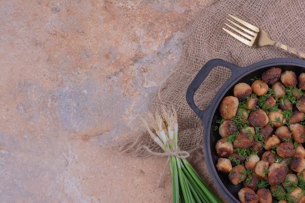 Khinkali caucasico fritto con erbe in una padella nera